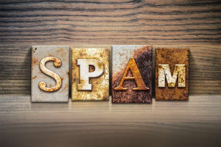 spammer: The word SPAM written in rusty metal letterpress type sitting on a wooden ledge background. Stock Photo