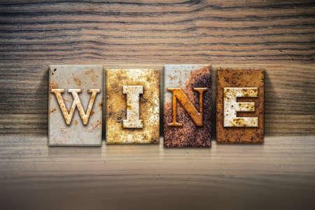 pinot noir: The word WINE written in rusty metal letterpress type sitting on a wooden ledge background. Stock Photo