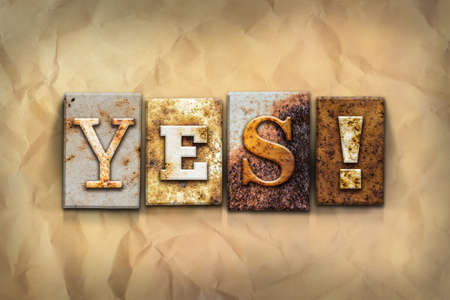 affirmative: The word YES! written in rusty metal letterpress type on a crumbled aged paper background. Stock Photo