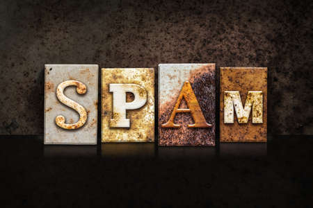 soliciting: The word SPAM written in rusty metal letterpress type on a dark textured grunge background. Stock Photo