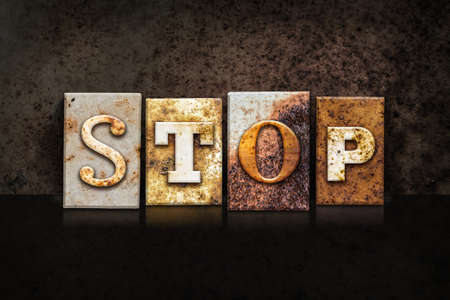 impede: The word STOP written in rusty metal letterpress type on a dark textured grunge background. Stock Photo