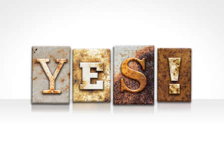 affirmative: The word YES! written in rusty metal letterpress type isolated on a white background.
