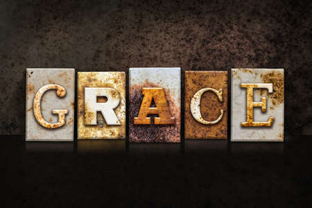 clemency: The word GRACE written in rusty metal letterpress type on a dark textured grunge background. Stock Photo