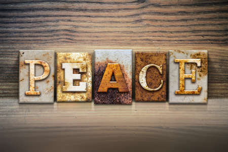 ceasefire: The word PEACE written in rusty metal letterpress type sitting on a wooden ledge background.