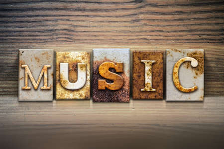 hymn: The word MUSIC written in rusty metal letterpress type sitting on a wooden ledge background. Stock Photo
