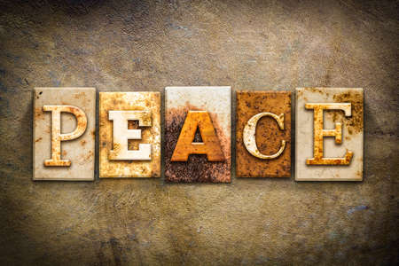 ceasefire: The word PEACE written in rusty metal letterpress type on an old aged leather background.