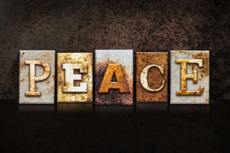 ceasefire: The word PEACE written in rusty metal letterpress type on a dark textured grunge background. Stock Photo
