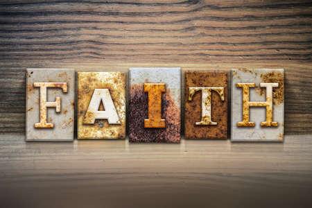 """Het woord """"geloof"""" geschreven in roestig metaal boekdruk type zittend op een houten richel achtergrond. Stockfoto"""