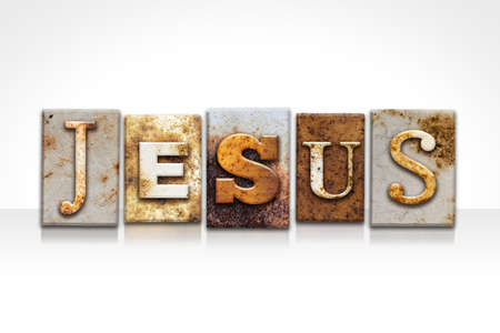 The name JESUS written in rusty metal letterpress type isolated on a white background.