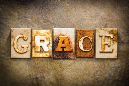 The word GRACE written in rusty metal letterpress type on an old aged leather background. Imagens