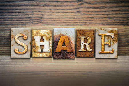 shared sharing: The word SHARE written in rusty metal letterpress type sitting on a wooden ledge background.