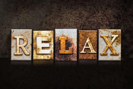 unwind: The word RELAX written in rusty metal letterpress type on a dark textured grunge background.