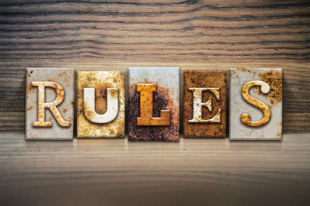 precedent: The word RULES written in rusty metal letterpress type sitting on a wooden ledge background. Stock Photo