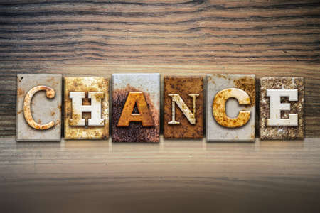 coincidence: The word CHANCE written in rusty metal letterpress type sitting on a wooden ledge background. Stock Photo