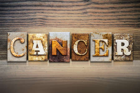 colon cancer: The word CANCER written in rusty metal letterpress type sitting on a wooden ledge background.