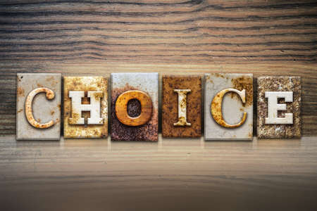 The word CHOICE written in rusty metal letterpress type sitting on a wooden ledge background. Stock Photo