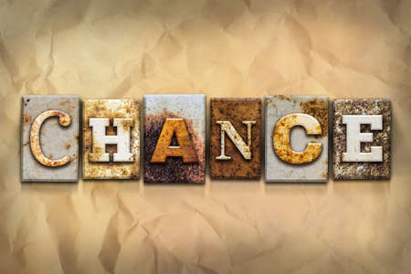 The word CHANCE written in rusty metal letterpress type on a crumbled aged paper background.