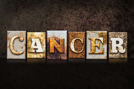colon cancer: The word CANCER written in rusty metal letterpress type on a dark textured grunge background.