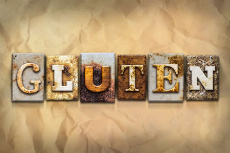 The word GLUTEN written in rusty metal letterpress type on a crumbled aged paper background. Stock Photo