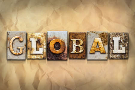 The word GLOBAL written in rusty metal letterpress type on a crumbled aged paper background.