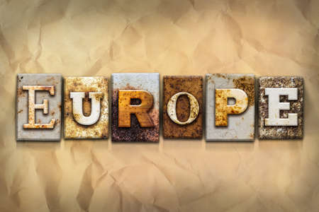 europe vintage: The word EUROPE written in rusty metal letterpress type on a crumbled aged paper background.