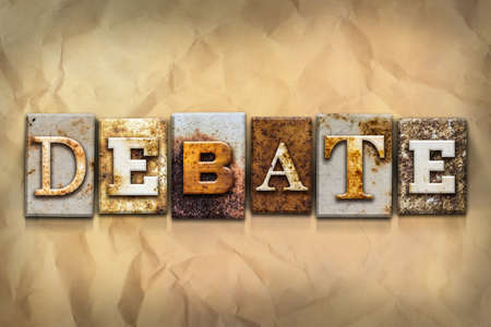 debate: The word DEBATE written in rusty metal letterpress type on a crumbled aged paper background.