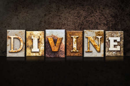godly: The word DIVINE written in rusty metal letterpress type on a dark textured grunge background.