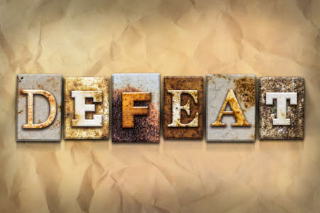 defeat: The word DEFEAT written in rusty metal letterpress type on a crumbled aged paper background.