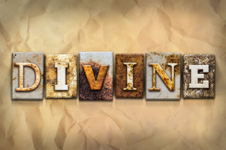 crumbled: The word DIVINE written in rusty metal letterpress type on a crumbled aged paper background. Stock Photo