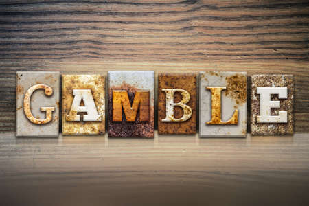gamble: The word GAMBLE written in rusty metal letterpress type sitting on a wooden ledge background.