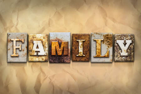 crumbled: The word FAMILY written in rusty metal letterpress type on a crumbled aged paper background.