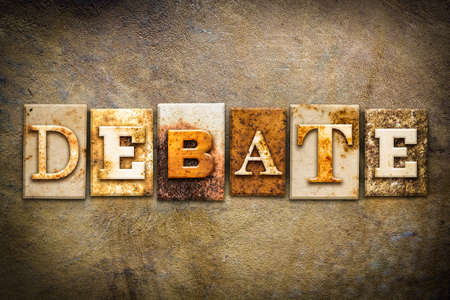 The word DEBATE written in rusty metal letterpress type on an old aged leather background.