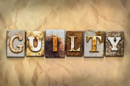 The word GUILTY written in rusty metal letterpress type on a crumbled aged paper background.