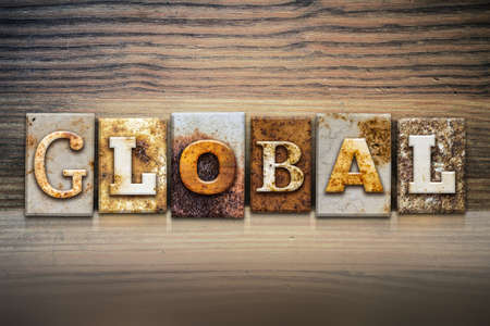 The word GLOBAL written in rusty metal letterpress type sitting on a wooden ledge background.