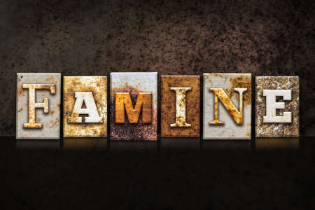 famine: The word FAMINE written in rusty metal letterpress type on a dark textured grunge background.