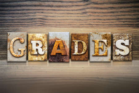 grades: The word GRADES written in rusty metal letterpress type sitting on a wooden ledge background.