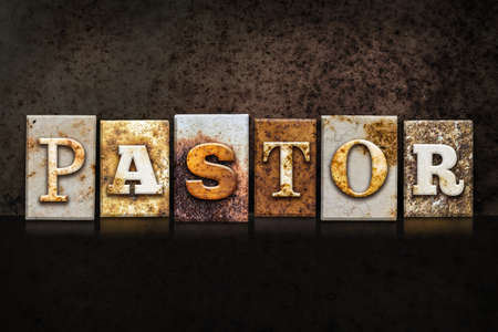 prayer background: The word PASTOR written in rusty metal letterpress type on a dark textured grunge background.
