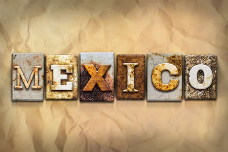 The word MEXICO written in rusty metal letterpress type on a crumbled aged paper background.