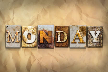 crumbled: The word MONDAY written in rusty metal letterpress type on a crumbled aged paper background. Stock Photo