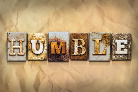 The word HUMBLE written in rusty metal letterpress type on a crumbled aged paper background.