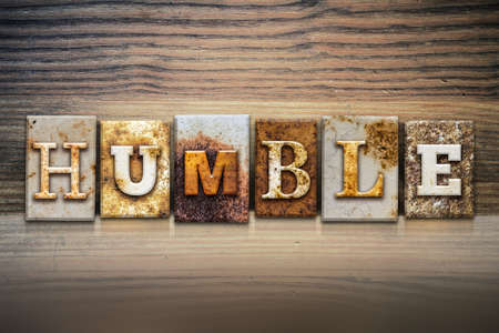 The word HUMBLE written in rusty metal letterpress type sitting on a wooden ledge background.