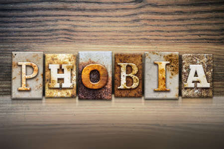 phobia: The word PHOBIA written in rusty metal letterpress type sitting on a wooden ledge background. Stock Photo