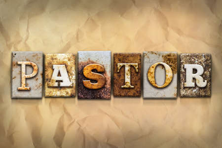 The word PASTOR written in rusty metal letterpress type on a crumbled aged paper background. Stock Photo