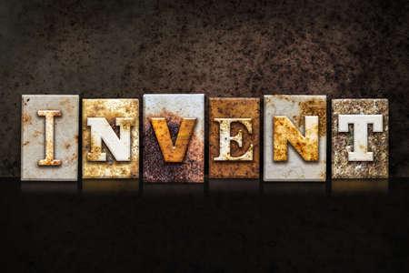 """Het woord """"INVENT"""" geschreven in roestig metaal letterzetseltype op een donkere getextureerde grunge achtergrond."""