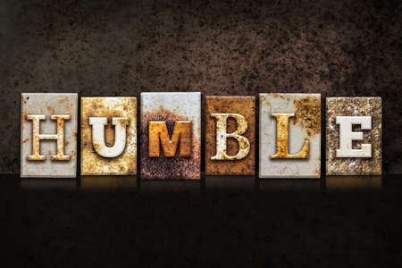 The word HUMBLE written in rusty metal letterpress type on a dark textured grunge background. Stock Photo
