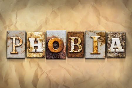 crumbled: The word PHOBIA written in rusty metal letterpress type on a crumbled aged paper background. Stock Photo