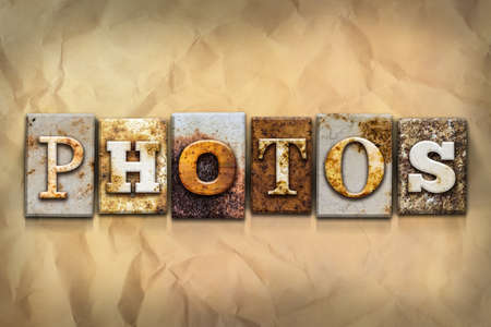 crumbled: The word PHOTOS written in rusty metal letterpress type on a crumbled aged paper background. Stock Photo