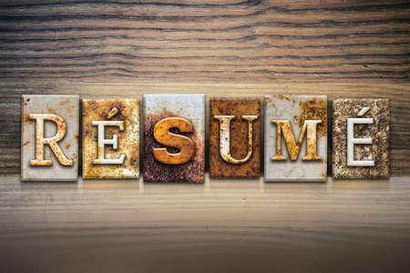 resumed: The word RESUME written in rusty metal letterpress type sitting on a wooden ledge background.