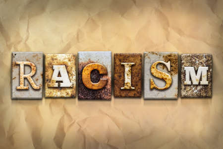 segregate: The word RACISM written in rusty metal letterpress type on a crumbled aged paper background. Stock Photo
