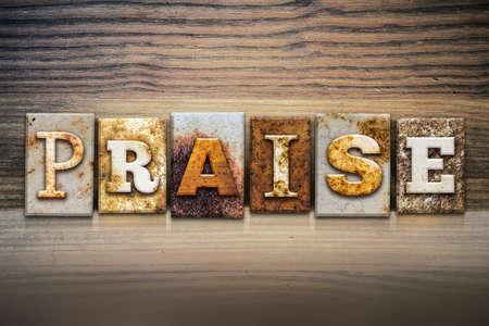 The word PRAISE written in rusty metal letterpress type sitting on a wooden ledge background.